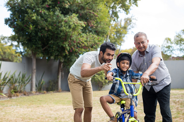 Two men teaching a child to ride a bike